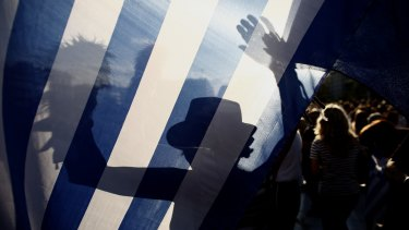 The shadow of a protester is seen on a Greek national flag during a pro European Union  demonstration in Athens on Monday.
