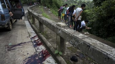 Blood stains the roadside as  civilians view unidentified bodies believed to have been executed and dumped in a ditch by militants.