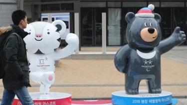 """A man passes by official mascots of the 2018 Pyeongchang Winter Games, a white tiger """"Soohorang"""" for the Olympic, and the Asiatic black bear """"Bandabi"""" for the Paralympic, in downtown Seoul."""