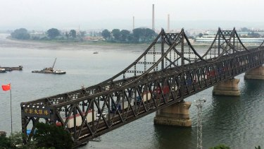 Tucks cross the friendship bridge connecting Dandong in China and Sinuiju in North Korea.