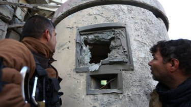 Afghan security personnel inspect the damage to the Spanish Embassy in Kabul on Saturday.