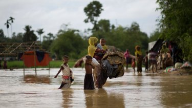 A Rohingya Muslim family walk with their belongings to find another shelter after their Bangladesh camp was inundated.
