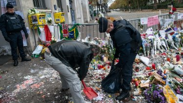 Police officers remove candles and flowers from the front of the Bataclan concert hall.