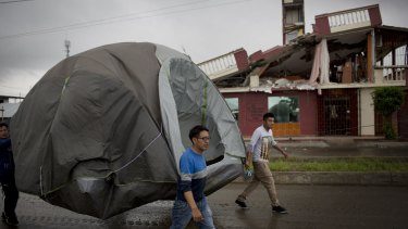 Volunteers move a tent to a new camp for residents affected one week after the devastating earthquake in Pedernales, Ecuador.