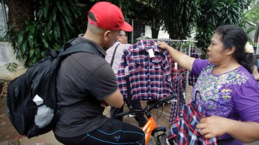 Santi Panggabean, right, does a brisk trade in Ahok's trademark plaid shirt. But the governor's popularity is not reflected in election polling.