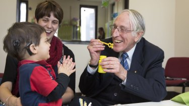 Graeme Clark who invented bionic ear with 2yr-old Declan Zemora who has just got his hearing.