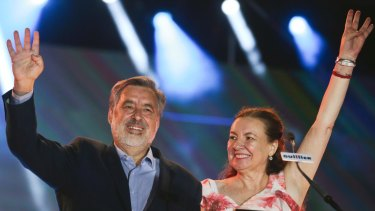 Presidential candidate Alejandro Guillier and his wife Cristina Farga wave to supporters during their closing campaign rally.
