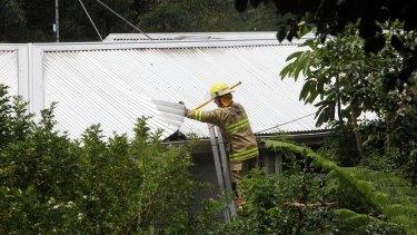 A fireman checks the roof of Kathy Jackson's house.