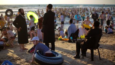 Ultra-Orthodox Jewish men and boys spend the day on a segregated beach in Netanya, Israel, earlier this month.