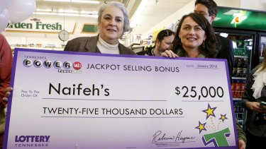 Rebecca Hargrove, left, president & CEO of the Tennessee Lottery, presents a check to Dana Naifeh, right, owner of Naifeh's Grocery in Munford, Tennessee where John Robinson bought the winning Powerball ticket.