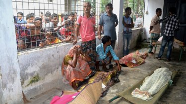 An elderly woman grieves next dead bodies at Mymensingh Medical College Hospital in the town of Mymensingh north of Dhaka, Bangladesh, on Friday.