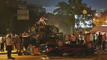 Tanks move into position as Turkish people attempt to stop them, in Ankara, Turkey, early on Saturday.