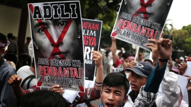 Protesters hold a defaced poster of Aung San Suu Kyi during a rally demanding justice for Rohingyas outside Myanmar's embassy in Jakarta in November.