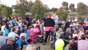 Hundreds gather at a Landsdale lake to pay tribute to two-year-old Sam Trott in 2014.