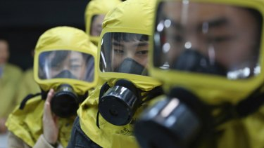 South Korean government officials wearing gas masks attend a civil defence drill against a possible North Korean chemical attack at their office in Seoul, South Korea, last week.