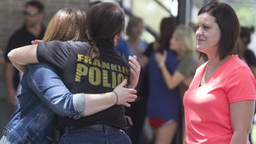 Franklyn police chief Sabria McGuire hugs Christian Wise as Britney Landry looks on outside a rosary service for Mayci Breaux in Franklin, Louisiana, on Friday.
