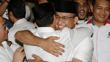 Jakarta's governor-elect Anies Baswedan, right, hugs his running mate  as unofficial results showed him defeating Ahok on April 19.