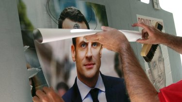 Christophe Sanz, a supporter French centrist presidential candidate Emmanuel Macron, sticks a campaign poster in Bayonne, south-western France.