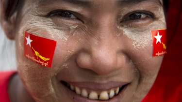 A member of Myanmar opposition leader Aung San Suu Kyi's National League for Democracy party smiles as she rides a trishaw during an election rally on Tuesday.