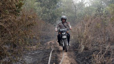 A policeman rides a motorcycle through a wildfire zone in Indralaya, South Sumatra.