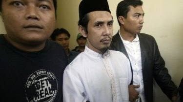 Self-described military commander of the south-east Asian terror network Jemaah Islamiyah Abu Dujana, centre, is escorted by police officers before his trial in Jakarta in 2007.