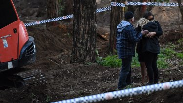 Faye Leveson (centre) is comforted by a family friend and her husband Mark Leveson (left) at the edge of the crime scene where human remains were unearthed.