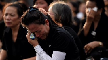 Women dressed in black weep outside the Grand Palace in Bangkok.
