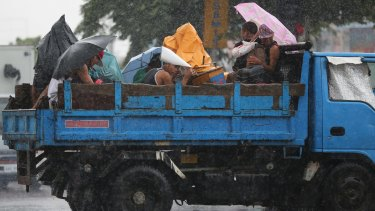 Filipinos riding on a truck take cover in Manila, Philippines on Monday as Typhoon Goni exits the country.