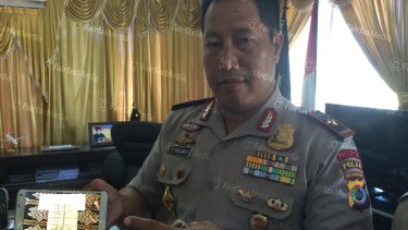 General Endang Sunjaya, police chief of Nusa Tenggara Timur province shows a mobile phone with a picture of the money on Tuesday.