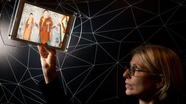 Professor Sarah Kenderdine demonstrates the augmented technology that reveals details of the Tang Dynasty cave wall mural.