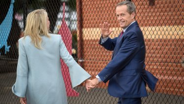 Opposition leader Bill Shorten, with wife Chloe, waves to media after voting in his electorate of Maribyrnong on Saturday.