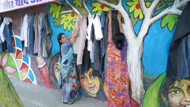Women hang donated clothes on the wall that is giving locals a taste for charity.