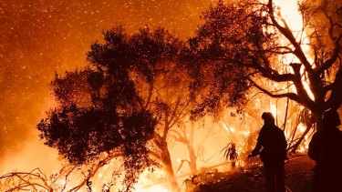 Santa Barbara firefighters knock down flames as they advance on homes in Carpinteria, California.