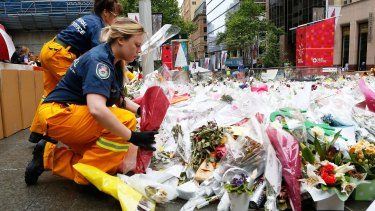 Volunteers remove flowers from Martin Place.