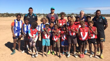 Giving back: Port Adelaide ruckman Paddy Ryder (centre) with Paul Vandenbergh (left), Byron Pickett (right) and kids at Yalata.