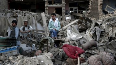 Men sit amid debris of their properties at the site of a truck bomb blast in Kabul on Friday.