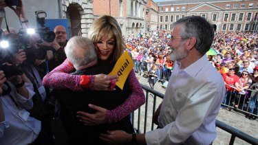 Drag queen and gay rights activist, Rory O'Neill (centre) hugs Senator David Norris with Sinn Fein president Gerry Adams looking on at Dublin Castle as they wait for the result of the referendum on Saturday.