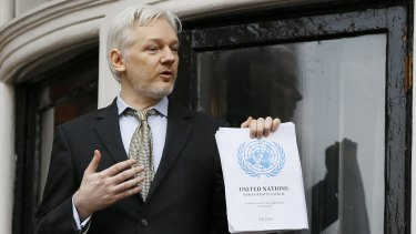 """Julian Assange holds the UN report saying the WikiLeaks founder has been been """"arbitrarily detained"""" by Britain and Sweden since December 2010."""
