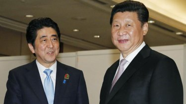 Chinese President Xi Jinping, right, shakes hands with Japanese Prime Minister Shinzo Abe in Jakarta in April.