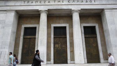 A Greek Orthodox priest walks past the headquarters of Greece's central bank, in Athens on Friday.