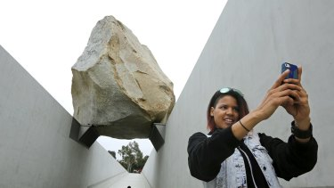 Monica Carter of Chicago takes a selfie in front of Michael Heizer's Levitated Mass boulder sculpture at the Los Angeles County Museum of Art.
