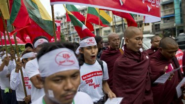 """Nationalists wearing T-shirts that say """"Stop Blaming Myanmar"""" and """"Boat People are not Myanmar"""" and Buddhist monks march in a protest rally in Yangon."""