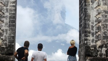 Tourists watch the Mount Agung volcano erupting at a temple in Karangasem.