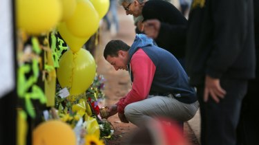 Stephanie Scott's fiance Aaron Leeson-Woolley visits a floral memorial on the gates of the Leeton High School.