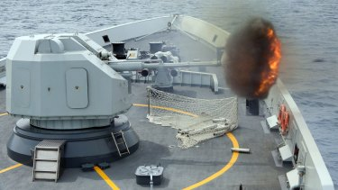 An anti-surface gunnery is fired from a Chinese missile frigate during military exercises by Singapore and Chinese navies in the South China Sea.