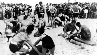 Exhausted bathers being revived by lifesavers on Bondi Beach, 6 February 1938.