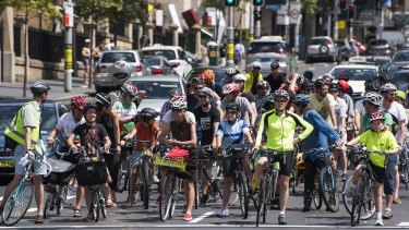 A coalition of cyclists gathers to protest against new bicycle policies and ride down College Street.