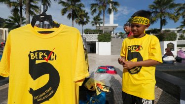 "Protesters sell ""Bersih"" T-shirts outside a national mosque during the rally in Kuala Lumpur, on Saturday."