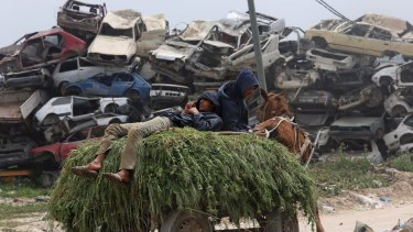 Farmers rest on a horse cart loaded with animal fodder as they pass a junkyard on their way to their barn, in  the Gaza Strip town of Beit Hanoun.