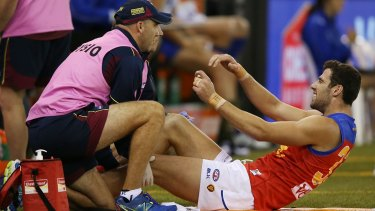 Michael Close of the Brisbane Lions reacts in pain after a knee injury during a round two match against North Melbourne on April 12.